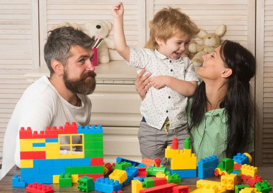 Pai e mãe brincando com o seu filho de lego
