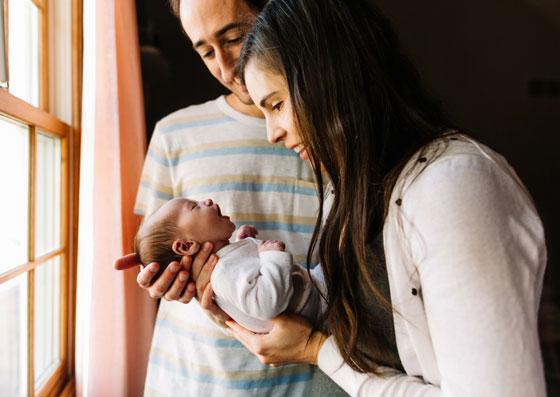 Mãe e pai segurando seu pequeno filho no colo
