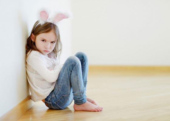 Filha sentada no chão emburrada