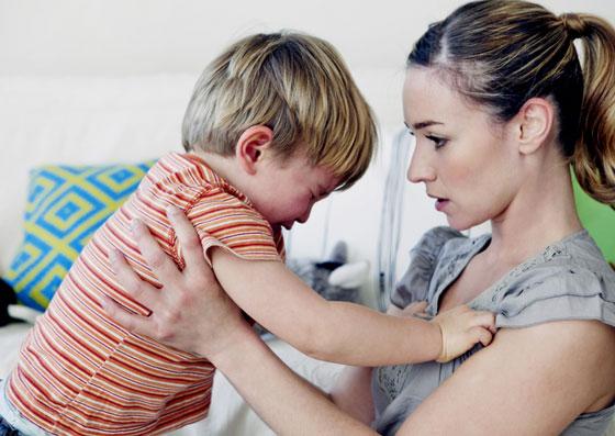 Mãe segurando seu filho, tendo um ataque de birra