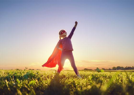 Garota vestida de super-herói com o braço para cima.