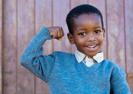 Garoto flexionando o seu braço demonstrando força e maturidade