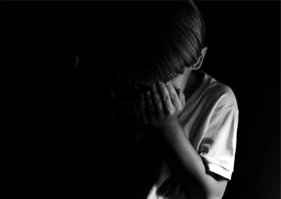 Garoto com a mão no rosto aparentando tristeza.