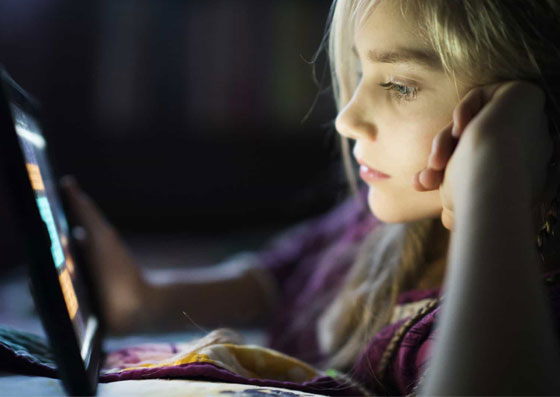 Garota olhando um tablet, exposta aos perigos da internet