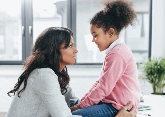 Mãe conversando com a filha, que esta sentada na mesa