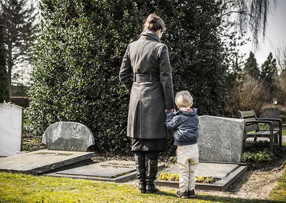 Mãe com o seu filho (criança), na frente de um túmulo de um familiar