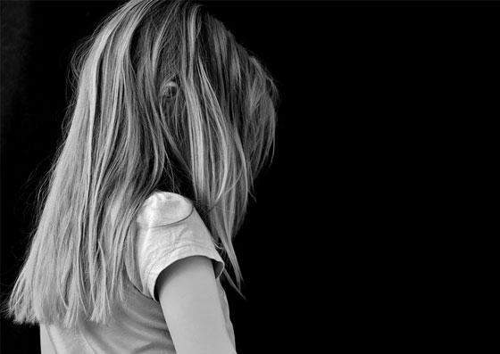 Criança de costas em uma sala escura