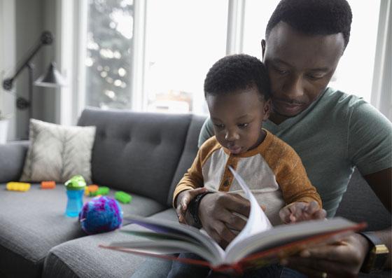 Pai lendo um livro para a sua criança (filho) sentados no sofá