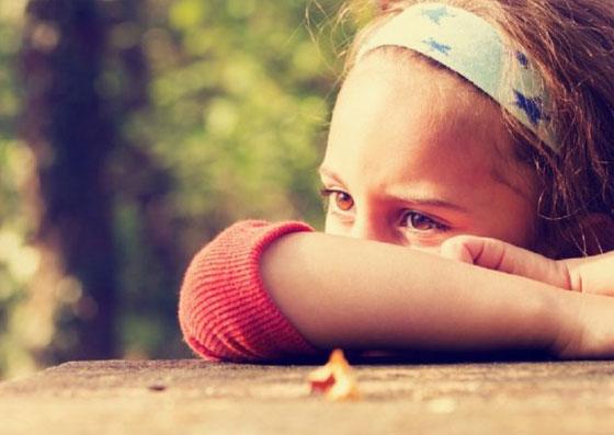 Criança com um olhar desolado, abatido e depressivo
