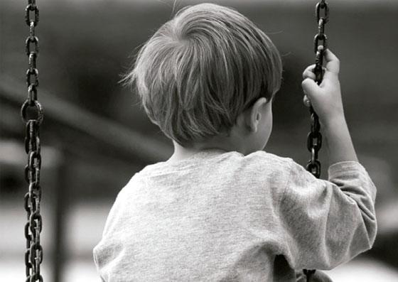 Criança sentado em um balanço, mas abatido e deprimido (setembro amarelo)