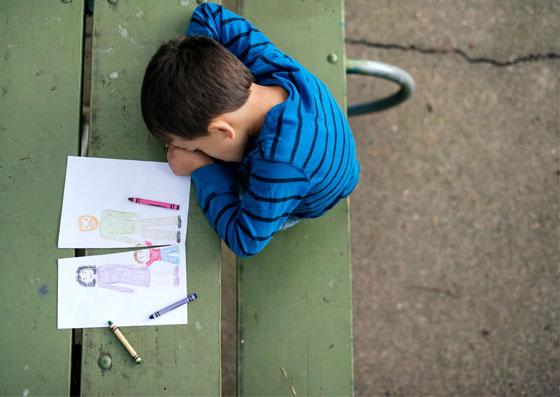 Filho sentado de cabeça baixa com um desenho rasgado no meio dos pais
