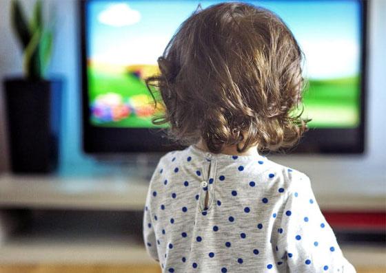 Criança (filho) na frente de uma televisão assistindo desenho