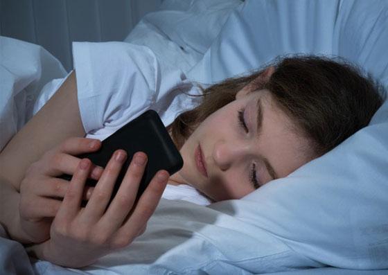 Menina vendo um celular antes de dormir