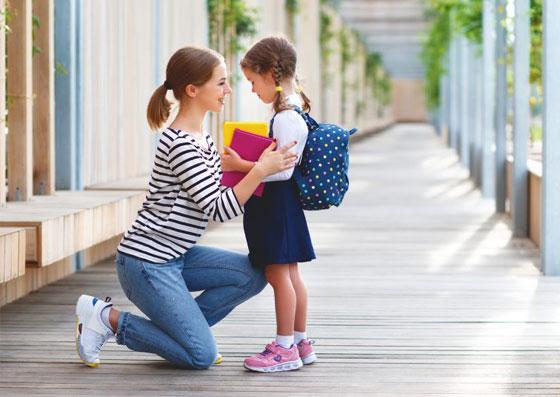 Mãe acalmando sua filha na volta às aulas