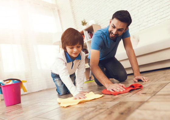 Pai e filho limpando o chão. Mostrando que a educação vem do exemplo