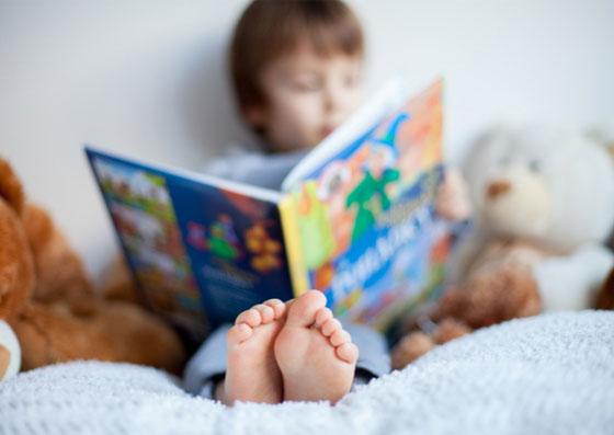 Criança lendo um livro sozinha