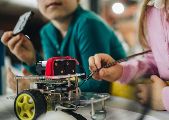 Crianças (alunos) aprendendo através do ensino da robotica